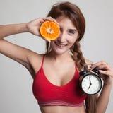 Schönes asiatisches gesundes Mädchen mit Orange und Uhr Lizenzfreies Stockbild