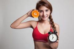 Schönes asiatisches gesundes Mädchen mit Orange und Uhr Stockfoto