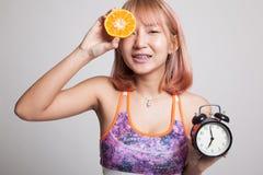 Schönes asiatisches gesundes Mädchen mit Orange und Uhr Lizenzfreie Stockfotos