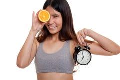 Schönes asiatisches gesundes Mädchen mit Orange und Uhr Stockfotografie