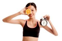 Schönes asiatisches gesundes Mädchen mit Orange und Uhr Lizenzfreie Stockfotografie