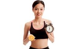 Schönes asiatisches gesundes Mädchen mit Orange und Uhr Stockbilder