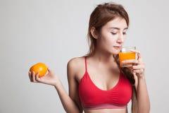 Schönes asiatisches gesundes Mädchen mit Orangensaft und orange Frucht Lizenzfreie Stockfotografie