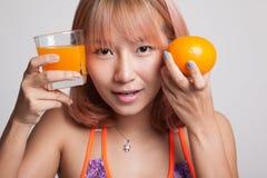 Schönes asiatisches gesundes Mädchen mit Orangensaft und orange Frucht Lizenzfreie Stockfotos