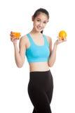 Schönes asiatisches gesundes Mädchen mit Orangensaft und orange Frucht Lizenzfreies Stockbild