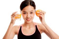 Schönes asiatisches gesundes Mädchen mit Orangensaft und orange Frucht Stockbild