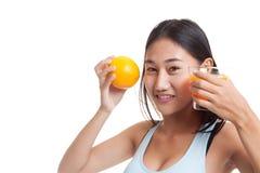 Schönes asiatisches gesundes Mädchen mit Orangensaft und orange Frucht Lizenzfreies Stockfoto