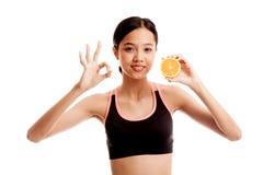 Schönes asiatisches gesundes Mädchenshow O.K. mit orange Frucht stockfoto