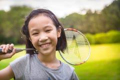 Schönes asiatisches Mädchen, das auf dem Naturhintergrund betrachtet die Kamera, Kind hält Federballschläger im Park, Ferien, Spo stockfotos