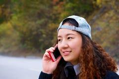 Schönes asiatisches Mädchen, das durch Handy nennt Lizenzfreie Stockfotos