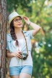 Schönes asiatisches Mädchen, das mit der Retro- fotografierenden Kamera, ou lächelt Lizenzfreies Stockfoto