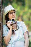 Schönes asiatisches Mädchen, das mit der Retro- fotografierenden Kamera, ou lächelt Lizenzfreie Stockbilder