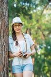 Schönes asiatisches Mädchen, das mit der Retro- fotografierenden Kamera, ou lächelt Stockfoto