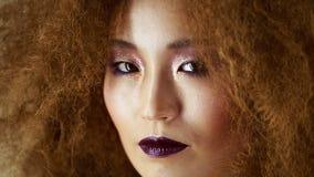 Schönes asiatisches Mädchen, das sicher die Kamera untersucht stock video
