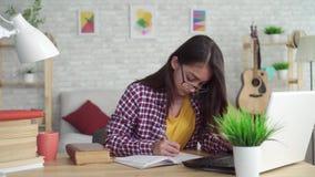 Schönes asiatisches Mädchen im Wohnzimmer zu Hause, sitzend am Tisch mit einem Laptop und einem Studieren stock video footage