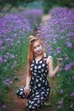 Schönes asiatisches Mädchen lächelt auf dem purpurroten Blumengebiet Lizenzfreies Stockfoto
