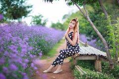 Schönes asiatisches Mädchen lächelt auf dem purpurroten Blumengebiet Stockfoto