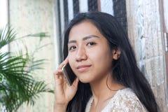 Schönes asiatisches Mädchen oder Frau, die jemand mit intelligentem Telefon O anrufen lizenzfreies stockfoto