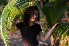 Schönes asiatisches Mädchen schaut durch die Palmblätter relax stockfotos