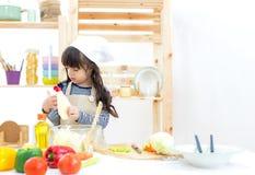 Schönes asiatisches Mädchenkind, das Gemüsesalat macht stockfotos