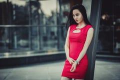 Schönes asiatisches Mädchenmodell im roten Kleid, das am modernen Glasartstadthintergrund aufwirft Stockfotos