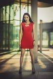 Schönes asiatisches Mädchenmodell im roten Kleid, das am modernen Glasartstadthintergrund aufwirft Sonniger Tag Stockfotos