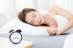 Schönes asiatisches Schlafenlügen der jungen Frau im Bett mit Kopf auf dem Kissen bequem und glücklich lizenzfreies stockbild