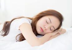 Schönes asiatisches Schlafenlügen der jungen Frau im Bett mit Kopf auf dem Kissen bequem und glücklich lizenzfreie stockfotografie