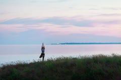 Schönes athletisches Mädchen, das Yoga gegen das Meer tut Stockfoto