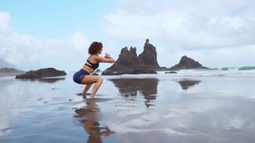 Schönes athletisches Mädchen in der sportlichen Kleidung auf dem Strand des Ozeans führt Hocken durch Gesunder Lebensstil Eignung stock footage