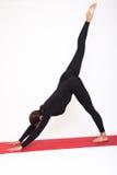 Schönes athletisches Mädchen im schwarzen Anzug, der Yoga tut Asanas Eka Pada Adho Mukha Svanasana - Hunde werfen Mündung unten m Stockfotografie