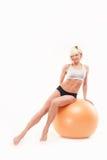 Schönes athletisches Mädchen sitzt auf dem fitball Stockfotografie