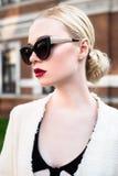Schönes attraktives blondes Mädchen in einem Kleid und in einem Barett draußen Lizenzfreies Stockfoto