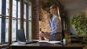 Schönes attraktives kaukasisches Mädchen sitzt auf dem Tisch mit einem Notizblock und einem Stift in den Händen Kreative Persönli stock video