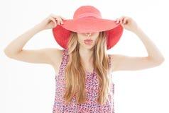 Schönes attraktives Mädchen versteckt ihr Gesicht hinter ihrem Sommerhut und zeigt ihre Zunge, die über Weiß lokalisiert wird lizenzfreie stockfotos