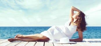 Schönes, attraktives und junges Mädchen, das im weißen Kleid auf a sitzt Lizenzfreie Stockfotografie