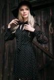 Schönes attraktives und stilvolles Mädchen, das den schwarzen Hut steht trägt, aufwerfend in der Stadt Nacktes Make-up, gut tägli Lizenzfreies Stockfoto