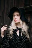Schönes attraktives und stilvolles Mädchen, das den schwarzen Hut steht trägt, aufwerfend in der Stadt Nacktes Make-up, gut tägli Stockfotos