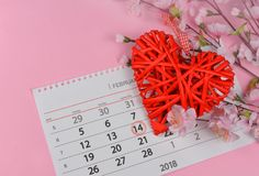 Schönes aus Weiden geflochtenes rotes Herz mit rosa Blumen auf einem rosa Hintergrund Lizenzfreie Stockfotos