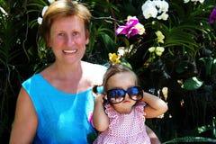 Schönes Baby, das auf dem Schoss einer Frau in den Hintergrundorchideen sitzt Frauenlachen Baby, das mit Sonnenbrille spielt Lizenzfreies Stockbild