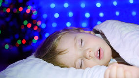 Schönes Baby, das auf der Bett Heiligen Nacht schläft Im Hintergrund, in den Lichtern und in den Girlanden der Tanne Lizenzfreies Stockfoto