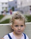 Schönes Baby, das auf der konkreten Bank sitzt Stockfotografie