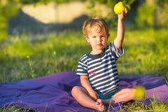 Schönes Baby, das draußen einen Apfel isst Lizenzfreie Stockbilder