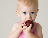 Schönes Baby, das eine Pflaume isst stockfoto