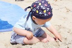 Schönes Baby, das mit dem Sand am Strand spielt Stockfotografie