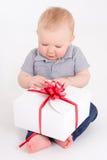 Schönes Baby, das mit Geschenkbox über Weiß sitzt Stockfotos