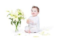 Schönes Baby, das mit Lilienblumen spielt Lizenzfreies Stockbild