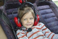 schönes Baby in den Kopfhörern, die im Cockpit einer Inspektion sitzen lizenzfreies stockbild