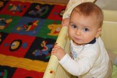 Schönes Baby der blauen Augen des blonden Haares in seinem Feldbett Stockfoto