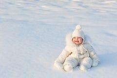 Schönes Baby in einer weißen Schneeklage, die auf frischem Schnee sitzt Stockfoto